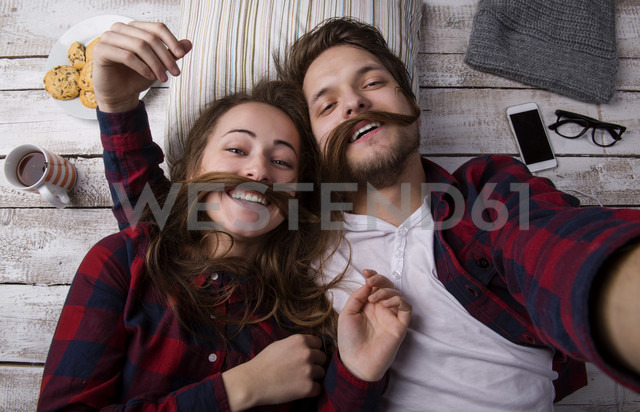 Portrait of young couple lying on the floor taking a selfie - HAPF000186 - HalfPoint/Westend61