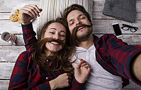 Portrait of young couple lying on the floor taking a selfie - HAPF000186