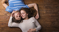 Young couple in love relaxing together on wooden floor - HAPF000192