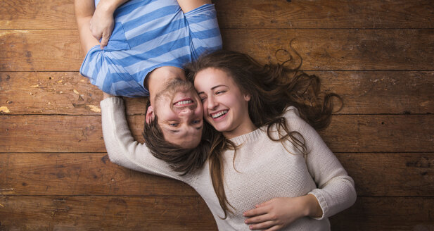Laughing young couple relaxing together on wooden floor - HAPF000195