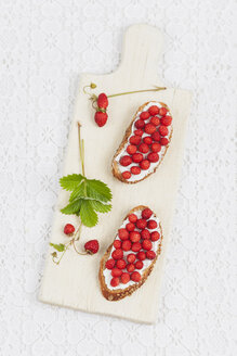 Slices of bread with cream cheese and woodland strawberries on chopping board - GWF004601