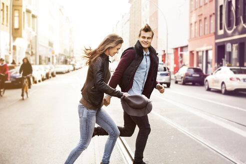 Germany, Berlin, happy couple crossing a street - GCF000126