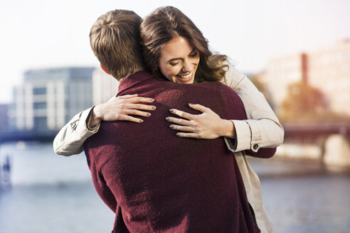 Germany, Berlin, happy young couple hugging at River Spree - GCF000144