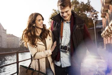 Germany, Berlin, happy young couple walking along River Spree - GCF000156