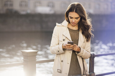 Germany, Berlin, young woman holding smartphone at River Spree - GCF000159