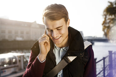 Germany, Berlin, young man on the phone at River Spree - GCF000162