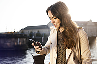 Germany, Berlin, young woman holding smartphone at River Spree - GCF000165