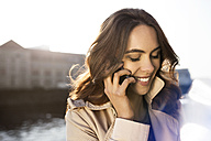 Germany, Berlin, young woman on the phone at River Spree - GCF000168