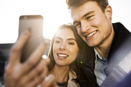 Smiling young couple taking a selfie outdoors - GCF000171