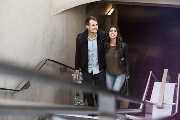 Germany, Berlin, smiling couple leaving underground station - GCF000186
