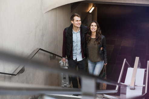 Germany, Berlin, smiling couple leaving underground station - GCF000186