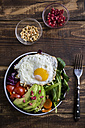Bowl with red cabbage, lamb's lettuce, carrot, tomato, avocado, fried egg, pine nut, feta cheese and pomegranate seeds, vegetarian - SARF002524