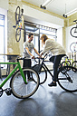 Client testing racing cycle in a custom-made bicycle store - JUBF000099
