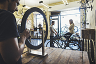 Mechanic, salesman and client in a custom-made bicycle store - JUBF000105