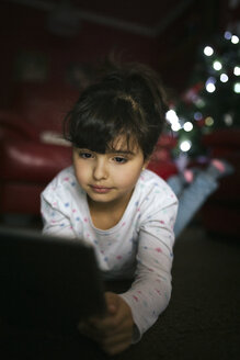 Portrait of little girl using digital tablet at home - MGOF001328