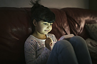 Portrait of little girl using games console at home - MGOF001331