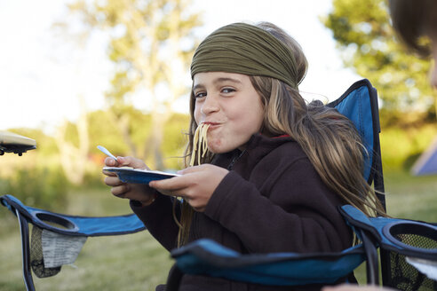 Girl eating spaghetti on a camping ground - TSFF000006