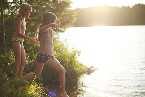Sweden, two girls jumping into the lake - TSFF000012