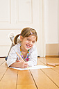 Portrait of laughing little girl lying on wooden floor with crayons and sheet of paper - LVF004510