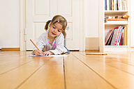 Portrait of smiling little girl lying on wooden floor painting with crayons - LVF004513