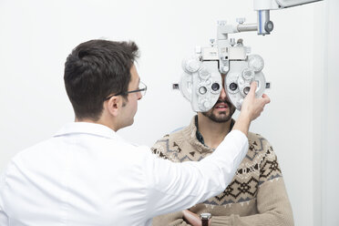 Optometrist examining eyesight of a man - ERLF000123