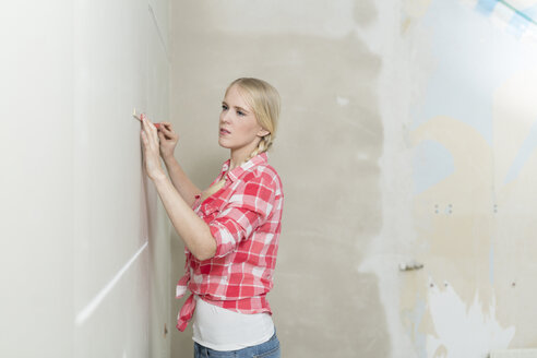 Young woman with pocket rule on construction site measuring wall - SHKF000484
