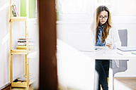 Young woman sitting at desk in her home office looking at smartphone - AKNF000037