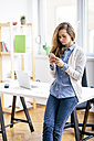 Young woman using smartphone in the office - AKNF000040
