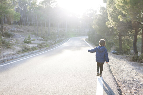 Spain, Siurana, back view of little boy walking on side line of empty country road - VABF000123