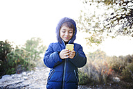 Spain, Siurana, portrait of smiling little boy looking at his smartphone - VABF000132