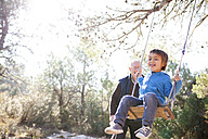 Spain, Siurana, little boy having fun on a swing while his grandfather watching him - VABF000135