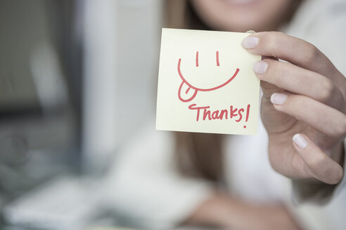 Close-up of woman holding a sticky note with a smiley face - ZEF008354