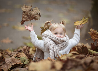 Happy blond girl with big scarf throwing autumn leaves in the air - NIF000068