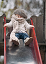 Portrait of little girl wearing big scarf and woolly hat on a slide - NIF000074