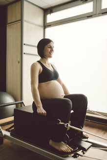 Pregnant woman doing Pilates exercises with a reformer pilates machine - RAEF000848