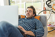 Portrait of young man lying on the couch using laptop - UUF006485