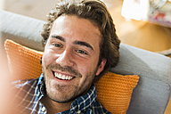 Portrait of smiling young man lying on the couch - UUF006488