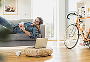 Young man lying on the couch at home looking at laptop - UUF006491