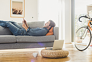 Young man lying on the couch at home looking at digital tablet - UUF006494