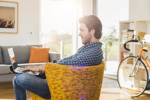 Young man sitting on an armchair in the living room using laptop - UUF006497