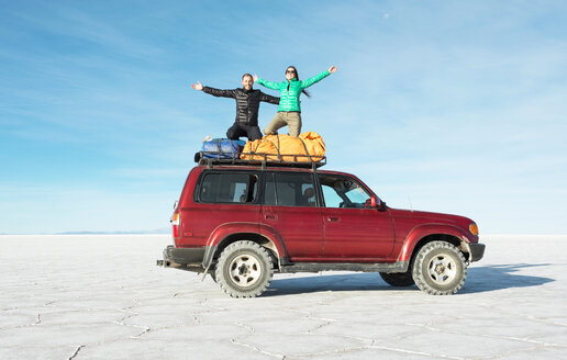 Bolivia, Salar de Uyuni, Couple kneeling on a 4x4 car - GEMF000713