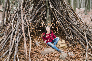 Spain, Barcelona, Santa Fe del Montseny, woman sitting in a hut watching autumn leaves in the air - GEMF000716