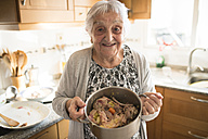 Portrait of smiling senior woman showing a cooking pot of Galician stew in the kitchen - RAEF000855
