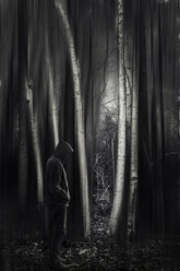 Man with hooded jacket in forest, black and white - DWIF000686