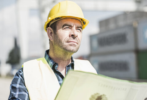 Man wearing hard hat holding document at container port - UUF006520