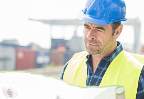 Man wearing hard hat reading document at container port - UUF006523