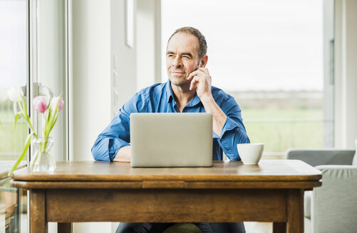 Businessman at home with laptop at wooden table thinking - UUF006541