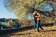 Happy couple embracing in autumn forest - CHAF001570