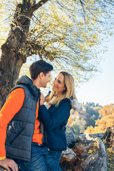 Happy couple enjoying autumn in a forest - CHAF001576