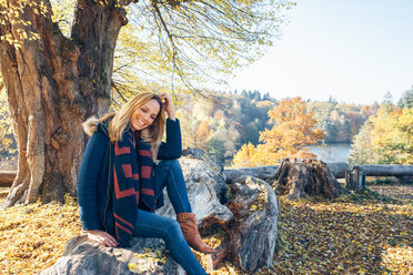 Smiling woman enjoying autumn in a forest sitting on a trunk - CHAF001579